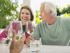 Happy middle aged couple having wine with friend at verandah tab